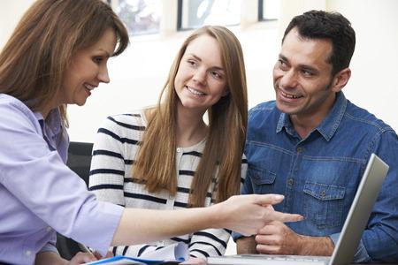planificacion: Pares que hablan con el consejero financiero de sexo femenino en oficina