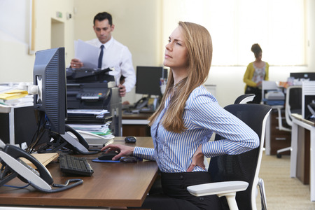 people sitting on chair: Businesswoman Working At Desk Suffering From Backache Stock Photo