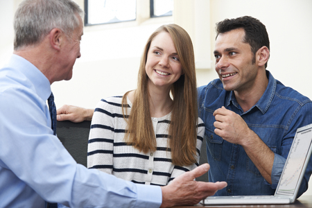 financial advice: Couple Talking With Financial Advisor In Office