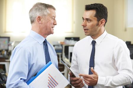 El hombre de negocios que tiene discusión con Mentor mayor en oficina Foto de archivo