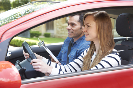 drive car: Woman Having Driving Lesson With Instructor