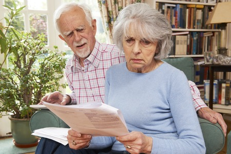credit crunch: Senior Couple Going Through Finances Looking Worried Stock Photo