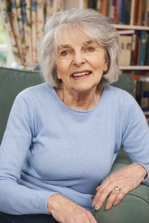 elderly adults: Portrait Of Smiling Senior Woman Sitting In Armchair
