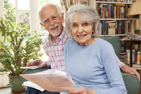 70s adult: Happy Senior Couple Reviewing Finances At Home