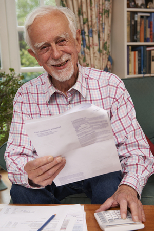70s adult: Senior Man Going Through Finances Looking Happy And Secure