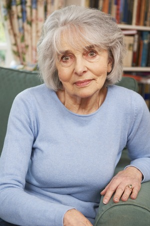 the ageing process: Portrait Of Senior Female Sitting In Armchair