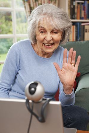 70s adult: Senior Woman Using Webcam To Talk With Family