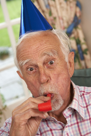 70s adult: Senior Man Celebrating With Party Hat And Blower