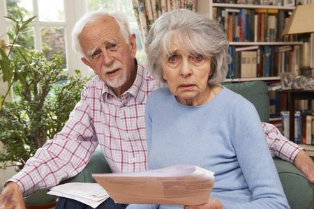 bills: Senior Couple Going Through Finances Looking Worried Stock Photo
