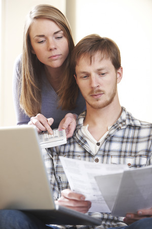 home finances: Serious Young Couple Looking At Home Finances