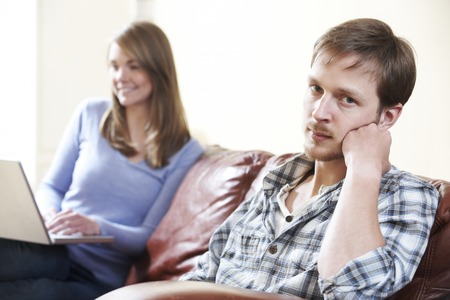 uses computer: Unhappy Man Sitting On Sofa As Partner Uses Computer