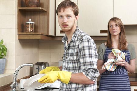 lavar trastes: Hombre De mala gana Lavar los platos en la cocina con el socio