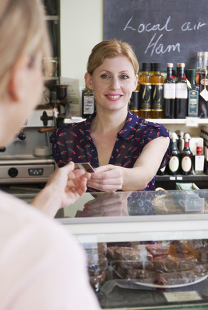 mid thirties: Customer Paying For Shopping In Delicatessen With Credit Card