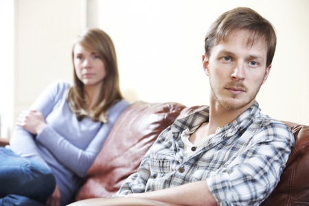 difficulties: Couple With Relationship Difficulties Sitting On Sofa
