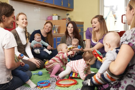 bebe sentado: Grupo de madres con beb�s en Playgroup Foto de archivo