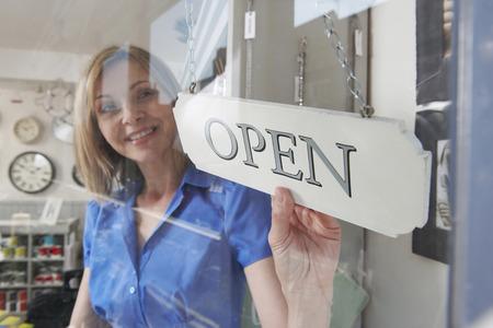 店の戸口にオープン サインを回して所有者を格納します。