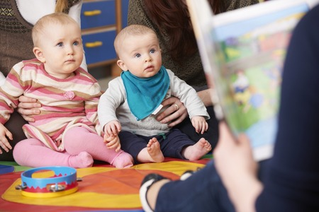 playgroup: Mothers With Children At Baby Group Listening To Story