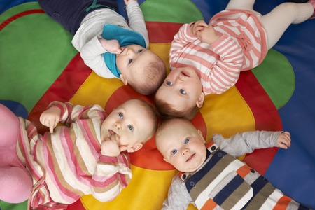 creche: Overhead View Of Babies Lying On Mat At Playgroup