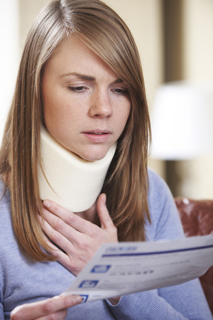 neck brace: Young Woman Wearing Neck Brace Reading Letter Stock Photo