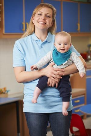 Portrait Of Nursery Worker Holding Baby photo