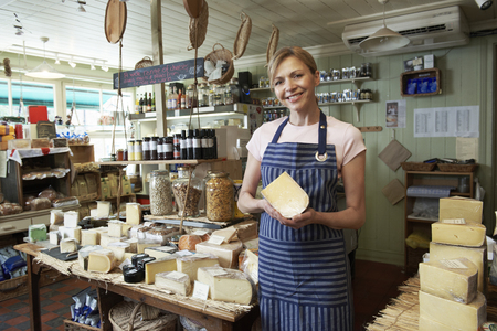 Owner Of Delicatessen Standing In Shop Holding Cheese