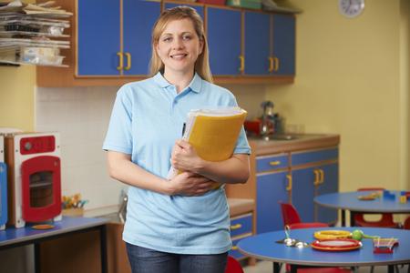 guardería: Trabajador cuidado de los niños de pie en cuarto de niños
