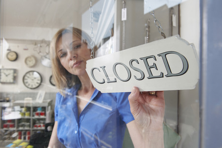 shop opening hours: Store Owner Turning Closed Sign In Shop Doorway Stock Photo