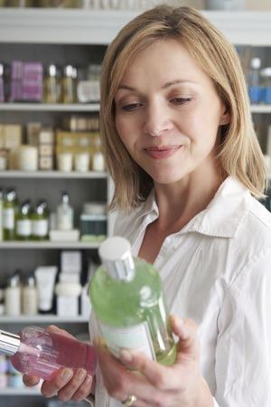 productos de belleza: Cliente femenino en departamento de la elección de los productos de belleza