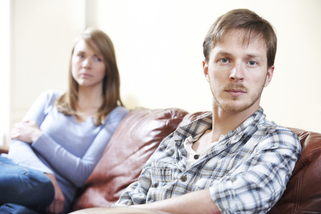 arguement: Couple With Relationship Difficulties Sitting On Sofa