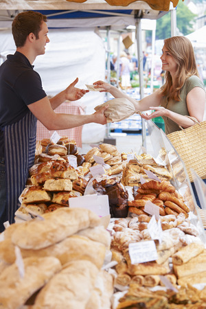Woman Buying Bread From Market Stall Stock Photo