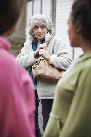 intimidated: Senior Woman Feeling Intimidated By Teenage Girls