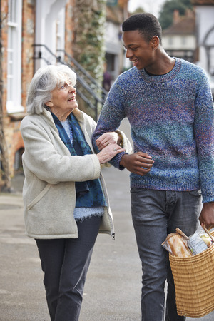 ancianos caminando: Adolescente que a la mujer mayor de compras para llevar