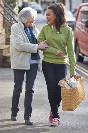 persona caminando: Adolescente a la mujer mayor para llevar Compras Foto de archivo