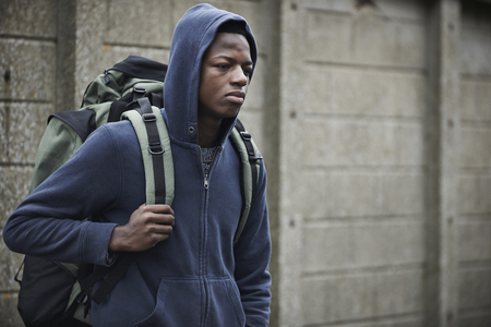 homeless man: Teenage Boy On The Streets With Rucksack Stock Photo