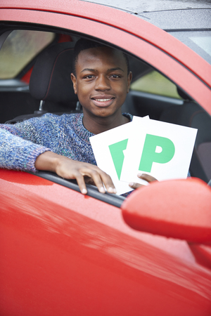 passed test: Teenage Boy Recently Passed Driving Test Holding P Plates