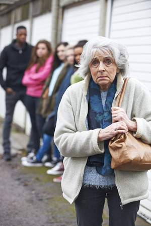 intimidated: Senior Woman Feeling Intimidated By Group Of Young People