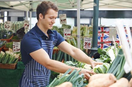 Man Arranging Display On Market Vegetable Stall