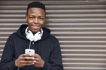 Adolescente que escucha la música y usar el teléfono en el ambiente urbano Foto de archivo