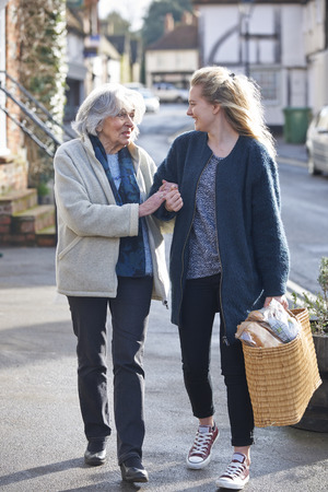 mixed race people: Teenage Girl Helping Senior Woman To Carry Shopping Stock Photo