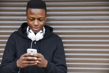 young guy: Teenage Boy Listening To Music And Using Phone In Urban Setting Stock Photo