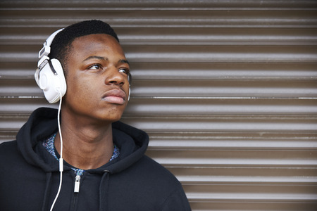 black male: Teenage Boy Listening To Music In Urban Setting