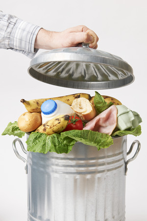 food waste: Hand Putting Lid On Garbage Can Full Of Waste Food Stock Photo
