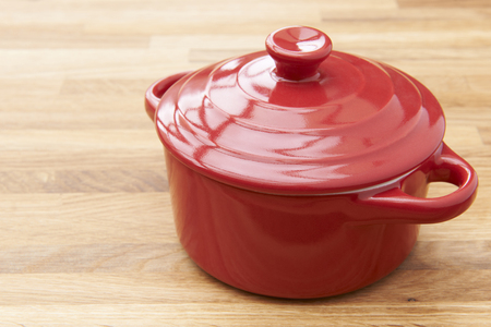 casserole dish: Red Casserole Dish On Wooden Surface Stock Photo