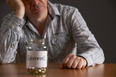 cuenta bancaria: Hombre deprimido Mirando a Jar Etiquetado de Retiro vacía