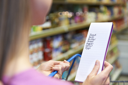 list: Close Up Of Woman Reading Shopping List In Supermarket Stock Photo