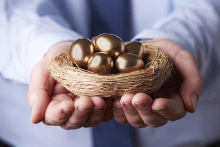 huevo: El hombre de negocios que sostienen la jerarquía completa de huevos de oro Foto de archivo