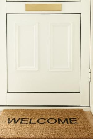stoop: Welcome Mat In Front Of Door To Home