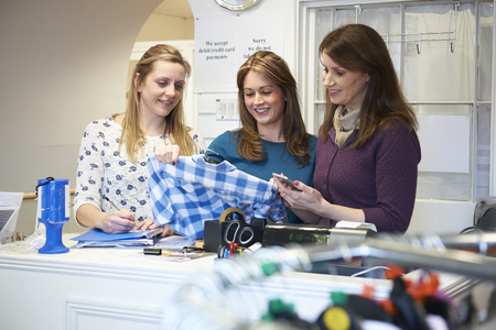 thrift store: Three Female Volunteers Workers In Charity Shop