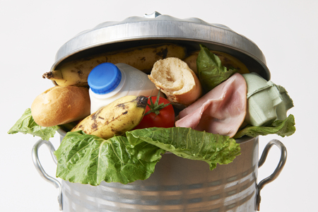 comida: Alimentos frescos en Cubo de basura para ilustrar Residuos Foto de archivo