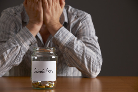 empty table: Man With Head In Hands Looking At Jar Labelled School Fees